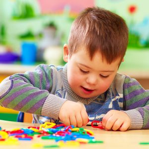 Boy with Downs syndrome playing with blocks